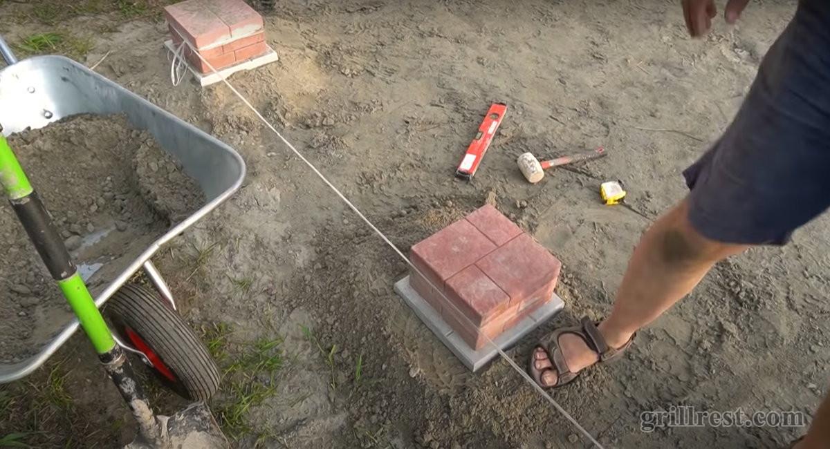 Промежуточные фундаментные блоки ставятся по уровню с помощью натянутой между углами верёвки