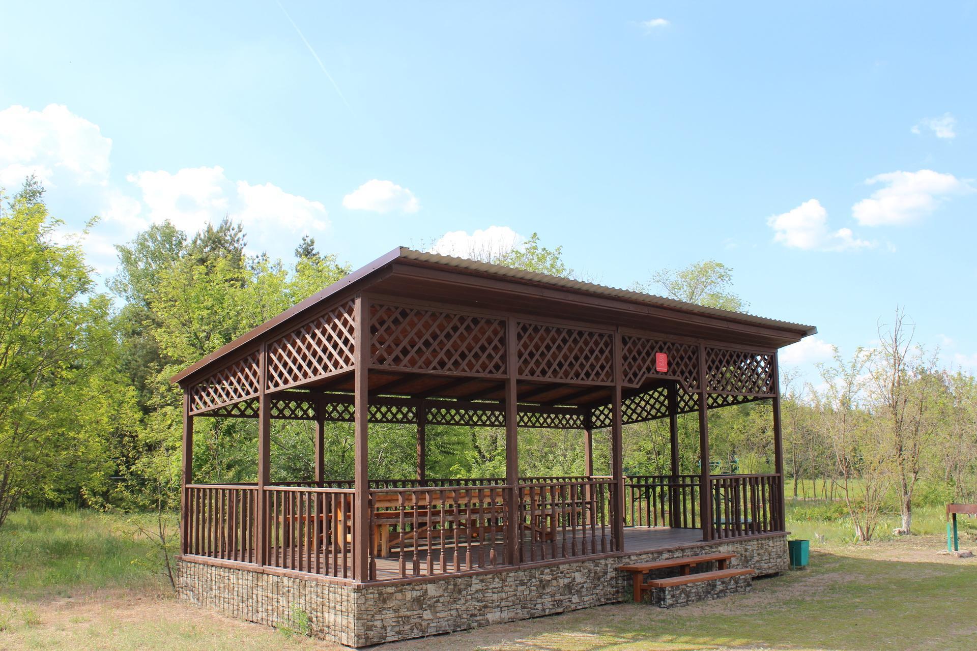 До 20 человек — одна бревенчатая и одна резная беседка площадью 3х8 метров каждая, мангалы расположены рядом со строениями